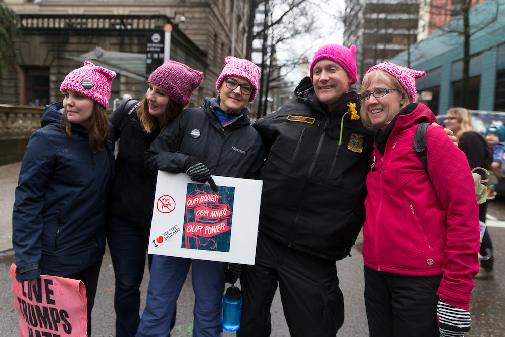 Portland Police Bureau officer Dan Spiegel poses with participants in Women's March on Portland on Saturday, Jan. 21, 2016 in downtown Portland, Ore. The march was held in support of a national women's march held in Washington, D.C.  Photo by Randy L. Rasmussen, © 2017.