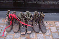 1987, Washington, DC, USA --- A red ribbon drapes across three pairs of combat boots in front of the Vietnam Veterans Memorial Wall in Washington DC. USA. --- Image by © Owen Franken/CORBIS