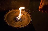 A woman light three sticks of incense, one for the past, one for the present and one for the future.  <br /> <br /> The first temple Ryōzen-ji (霊山寺) of the Shikoku Pilgrimage, 88 temples associated with the Buddhist monk Kūkai (Kōbō Daishi) on the island of Shikoku, Naruto,Tokushima Prefecture, Japan<br /> <br /> <br /> <br /> <br /> En kvinna t&auml;nder tre r&ouml;kelser, en f&ouml;r det f&ouml;rg&aring;ngna, en f&ouml;r nuet och en f&ouml;r framtiden. <br /> Tempel nummer 1, Ryōzen-ji (霊山寺)<br /> <br /> Pilgrimsvandring till 88 tempel p&aring; japanska &ouml;n Shikoku till minne av den japanske munken Kūkai (Kōbō Daishi). <br /> <br /> Fotograf: Christina Sj&ouml;gren<br /> Copyright 2018, All Rights Reserved