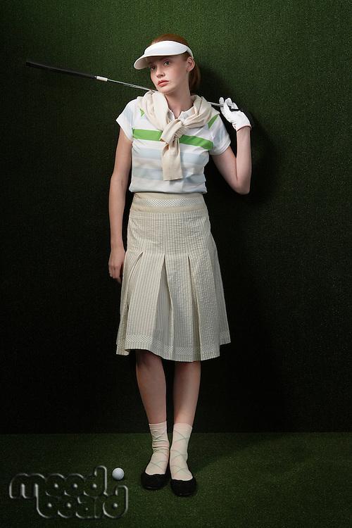 Woman in visor holding golf club behind shoulders portrait