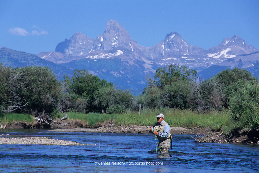 08435-B. An angler fly fishes for trout on east Idaho's Teton River, with the Teton Range of Wyoming in the background.