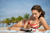 Teenage girl (16-17) reading magazine lying on beach