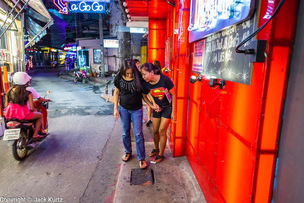 4 JUNE 2013 - BANGKOK, THAILAND:  Women walk down an alley past a go-go bar in the Patpong Night Bazaar in Bangkok. Patpong was one of Bangkok's notorious red light districts but has been made over as a night market selling clothes, watches and Thai handicrafts. The old sex oriented businesses still exist but the area is now better known for its night shopping.      PHOTO BY JACK KURTZ