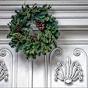Christmas Wreath with decorations on front door in Greenwich Village.<br /> <br /> The tradition of hanging wreath during Christmas is essentially a Christian ritual. This is done during the Christmas season, traditionally used to prepare for the coming of Christ, also known as the Advent season in Christianity. <br /> <br /> Traditionally, the Christmas wreaths were made of evergreen leaves, which are still symbolize the permanence of life.<br /> <br /> A traditional wreath is a circle, which means that there is no beginning or end and that God is eternal.