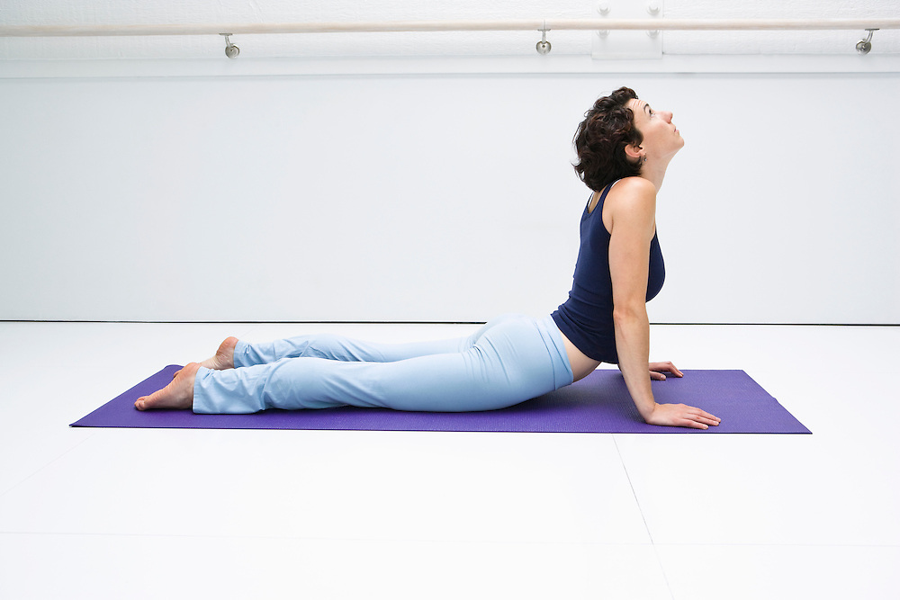 Young woman doing the Cobra pose in a white room on a yoga mat.
