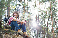 Full length of smiling male hiker looking away while sitting on cliff in forest