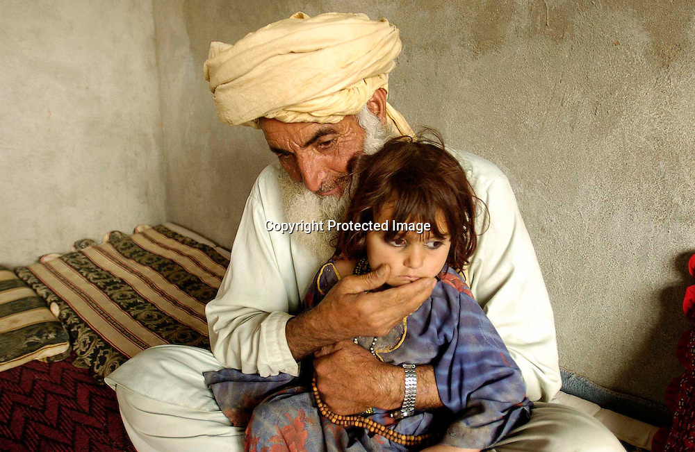 Asaldin holds Bibi Rashida(3),  the daughter  of his son Diliwar at their home in the the town of Yakubi in the district of Khost, Afghanistan May 2, 2005. Dilawar, a 22-year-old farmer and part-time taxi driver, died in December 2002 while being held in the main United States air base at Bagram, north of Kabul. His death was ruled a homicide by the Army medical examiner.<br />