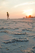 A girl takes a run across the beach at sunset.