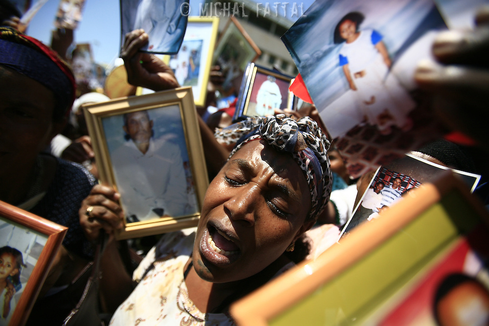 Israeli Ethiopian Jews hold photos of their relatives and shout slogans during a demonstration next to the Prime Minister office in Jerusalem, August 2008.