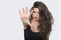 Portrait of a young female gesturing stop sign over gray background