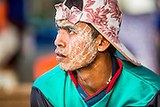 30 APRIL 2013 - MAHACHAI, SAMUT SAKHON, THAILAND:   A Burmese worker with a pattern of thanaka powder on his face in the Thai fishing industry in port in Mahachai, Samut Sakhon province, Thailand. The Thai fishing industry is heavily reliant on Burmese and Cambodian migrants. Burmese migrants crew many of the fishing boats that sail out of Samut Sakhon and staff many of the fish processing plants in Samut Sakhon, about 45 miles south of Bangkok. Migrants pay as much $700 (US) each to be smuggled from the Burmese border to Samut Sakhon for jobs that pay less than $5.00 (US) per day. There have also been reports that some Burmese workers are abused and held in slavery like conditions in the Thai fishing industry.         PHOTO BY JACK KURTZ