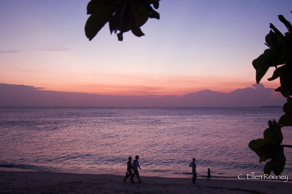 People walking on the beach at sunset.  Stone Town, Zanzibar, Tanzania