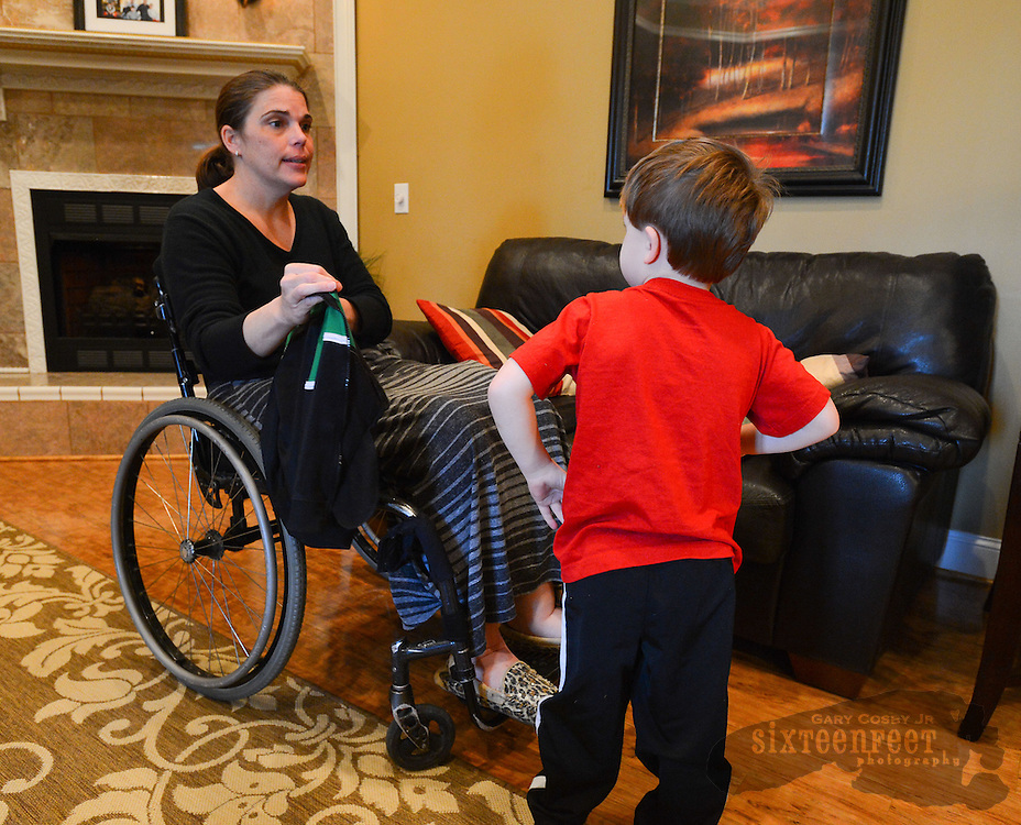 Gary Cosby Jr./Decatur Daily    Courtney Carpenter Boyll was a rising star athlete in 1994 when a car wreck left her paralyzed.   Twenty years later she is a wife, mother of three and third grade teacher and does it all as a paraplegic.  Max decides he would rather not put on a jacket being offered by Courtney as they get ready to go out for the evening.