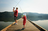 JEROME A. POLLOS/Press..Andrew Carney, 4, reels in a fish as his father Chris Carney tries to set the hook on another Wednesday on a dock at Upper Twin Lake. On his second outing, the young Carney reeled in six fish within the first hour.