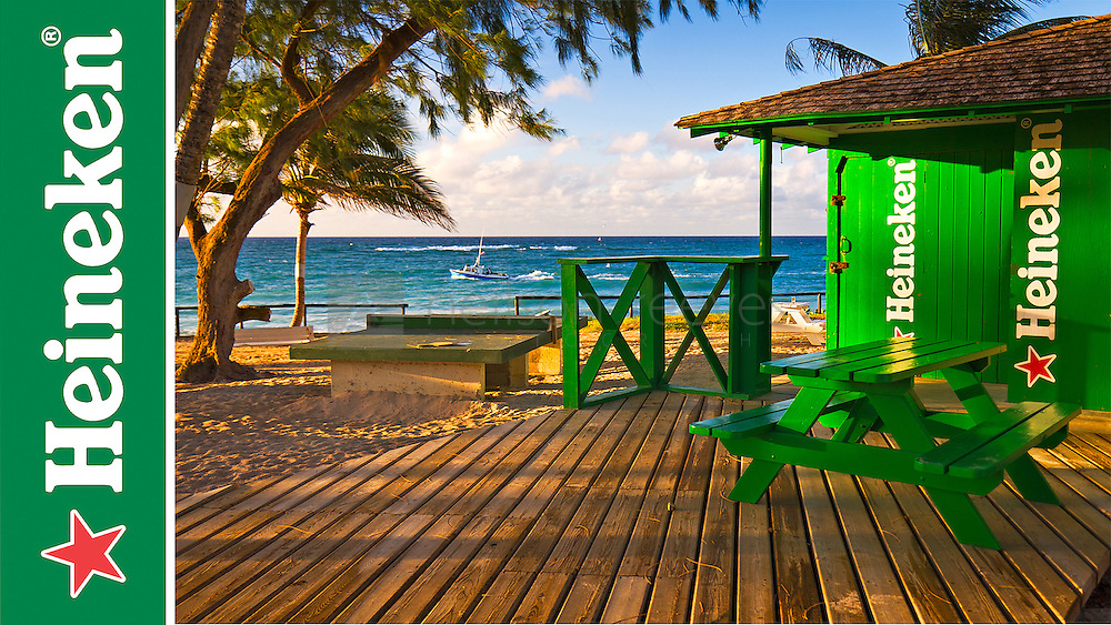 Image taken from the beach features a green bar with heineken branding and table in the foreground and the beach and the see in the background. photograph taken in barbados with blue sky and beach features a table tennis table