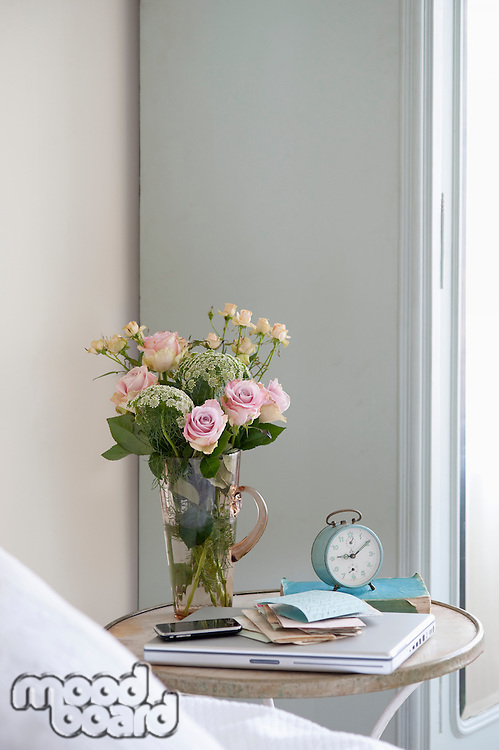 Roses in vase on bedside table with books and alarm clock