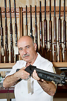 Mature gun merchant with rifle looking away