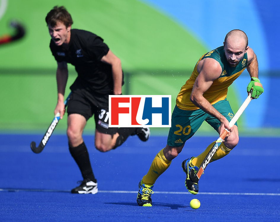 Australia's Matthew Swann controls the ball as New Zealand's Hayden Phillips chases during the men's field hockey Australia vs New Zealand match of the Rio 2016 Olympics Games at the Olympic Hockey Centre in Rio de Janeiro on August, 6 2016. / AFP / MANAN VATSYAYANA        (Photo credit should read MANAN VATSYAYANA/AFP/Getty Images)