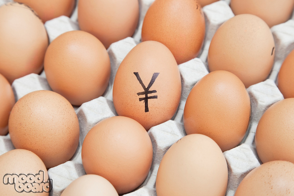 Yen currency sign on egg surrounded by plain brown eggs in carton