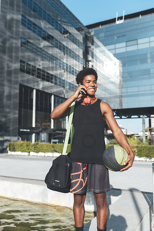 Young afro man talking by phone, red headphones, a basket ball and a bag waiting friends in urban scenery
