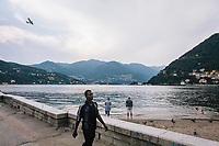 COMO, ITALY - 21 JUNE 2017: A Sub-Saharan migrant (left) is seen here walking by Lake Como while tourists enjoy the water, in Como, Italy, on June 21st 2017.<br /> <br /> Residents of Como are worried that funds redirected to migrants deprived the town's handicapped of services and complained that any protest prompted accusations of racism.<br /> <br /> Throughout Italy, run-off mayoral elections on Sunday will be considered bellwethers for upcoming national elections and immigration has again emerged as a burning issue.<br /> <br /> Italy has registered more than 70,000 migrants this year, 27 percent more than it did by this time in 2016, when a record 181,000 migrants arrived. Waves of migrants continue to make the perilous, and often fatal, crossing to southern Italy from Africa, South Asia and the Middle East, seeing Italy as the gateway to Europe.<br /> <br /> While migrants spoke of their appreciation of Italy's humanitarian efforts to save them from the Mediterranean Sea, they also expressed exhaustion with the country's intricate web of permits and papers and European rules that required them to stay in the country that first documented them.