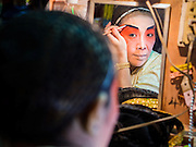 "18 AUGUST 2014 - BANGKOK, THAILAND: A member of the Lehigh Leng Kaitoung Opera troupe is reflected in a mirror while she applies her makeup before a performance at Chaomae Thapthim Shrine, a small Chinese shrine in a working class neighborhood of Bangkok. The performance was for Ghost Month. Chinese opera was once very popular in Thailand, where it is called ""Ngiew."" It is usually performed in the Teochew language. Millions of Chinese emigrated to Thailand (then Siam) in the 18th and 19th centuries and brought their culture with them. Recently the popularity of ngiew has faded as people turn to performances of opera on DVD or movies. There are still as many 30 Chinese opera troupes left in Bangkok and its environs. They are especially busy during Chinese New Year and Chinese holiday when they travel from Chinese temple to Chinese temple performing on stages they put up in streets near the temple, sometimes sleeping on hammocks they sling under their stage. Most of the Chinese operas from Bangkok travel to Malaysia for Ghost Month, leaving just a few to perform in Bangkok.     PHOTO BY JACK KURTZ"