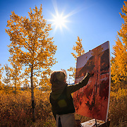 Hadley Rampton applies oil to canvas at Ox Bow Bend in Grand Teton National Park, Wyoming.
