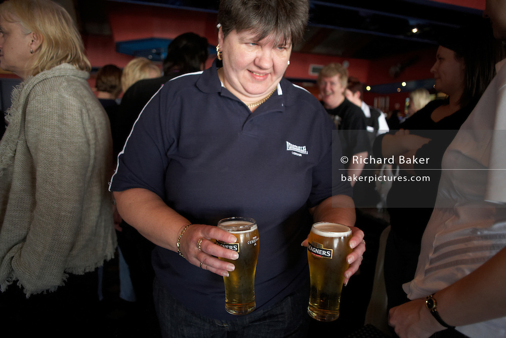 A butch Ladies darts player returns from bar with two pint glasses full of lager beer during England Open tournament