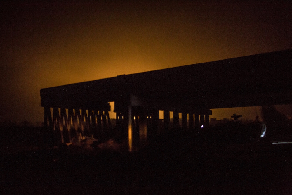 PERVOMAISKE, UKRAINE - NOVEMBER 19, 2014: The sky lights up due to shelling near the Donestk airport behind the bridge being used as a base by the Dnipro-1 brigade, a pro-Ukraine militia, in Pervomaiske, Ukraine. CREDIT: Brendan Hoffman for The New York Times