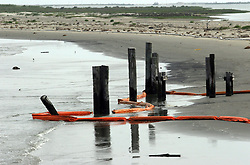 13 May 2010. Grand Isle, Lafourche Parish, Louisiana. <br /> Oil containment booms lie uselessly washed up on an inland tidal beach in Grand Isle. Fierce tidal currents and changeable weather makes it virtually impossible to keep booms in place around the parish. The first sticky  spots of oil surfaced on the west of the Mississippi river and have been confirmed up and down the beaches of Jefferson and Lafourche parishes. Oil from the Deepwater Horizon catastrophe is evading booms laid out to stop it thanks in part to the dispersants which means the oil travels at every depth of the Gulf. <br /> Photo credit; Charlie Varley/varleypix.com