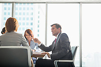 Businessman discussing with female team in conference room