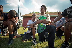 Jordan Beverly, 12  right, and Robert Conner 3rd, 13 watch football practice in River Rouge, Detroit,  August 15, 2012.  They both suffer from asthma and were sidelined for not getting their physical examination before practice. Many of his kids have asthma and the coach has to constantly monitor and ask them if they need inhalers during practice.