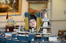 Bonham's worker Jaine Heggie dons a captains cap in preparation for the nautical collection auction at Bonham's in Edinburgh on November 15th pictured inspecting a mid 20th century model of Russian battleship 'Admiral Oushavov' which is up for sale.<br /> <br /> © Dave Johnston/ EEm