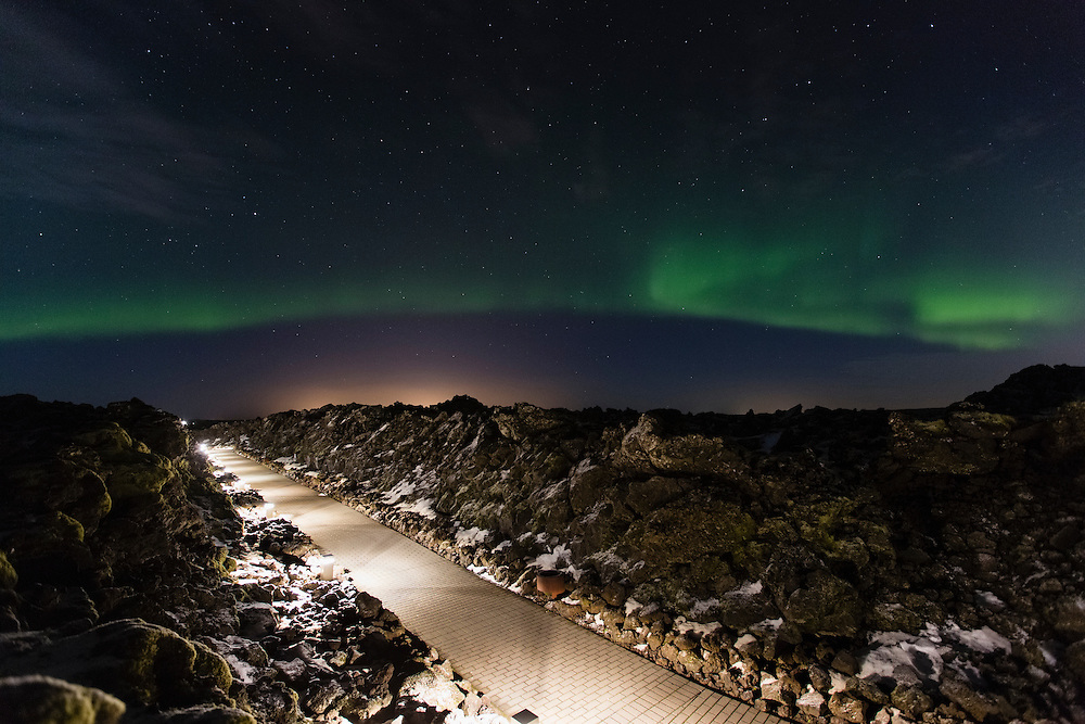 Aurora Borealis over a lit path, Iceland.