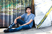 Outdoor portrait against graffiti mural of young Mexican-American male by Gerard Harrison.