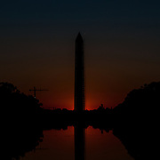 The sun below the horizon casts a predawn glow behind the base of the Washington Monument. Looking down the Reflecting Pool from the Lincoln Memorial. This shot was taken during the fall equinox, when the sun rises directly to the east and therefore lines up with the National Mall.