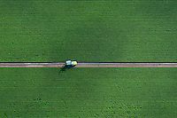 A truck on a dirt road that cuts through a crop field in Redland. Miami-Dade Agriculture.