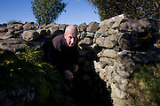Tattoed hermit Tom Leppard emerges from the entrance of his secret makeshift hideaway shelter on Skye, Scotland.