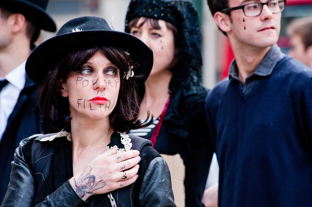 London, UK - 15 June 2012: an activist with a writing on her face reading 'Poverty is filth!' during the Carnival of Dirt. More than 30 activist groups from London and around the world have come together to highlight the alleged illicit deeds of mining and extraction companies.