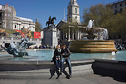 Lovers kiss near the fountains in Trafalgar Square, London.
