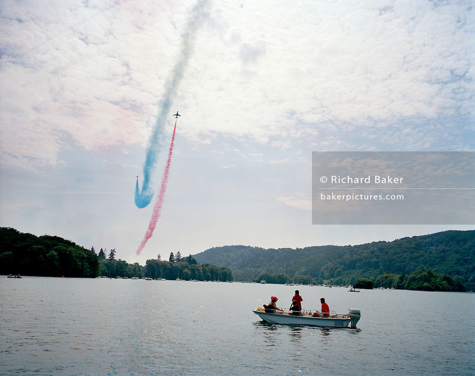 The Red Arrows, Britain's RAF aerobatic team, perform their public display over a lake and boating landscape.