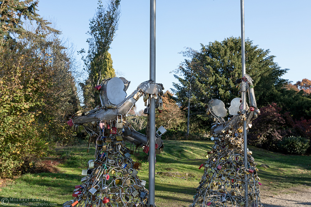 "Love in the Rain is a sculpture created by Bruce Voyce and is currently on display at Queen Elizabeth Park in Vancouver, British Columbia, Canada. The sculpture is for the attachment of ""love locks"" which couples can attach and then dispose of the keys in a nearby receptacle.  Previously the locks were becoming a problem on fences and other structures in the city."