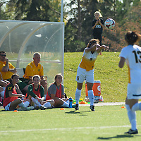 3rd year defender Angela Lalonde (5) of the Regina Cougars makes a sideline throw as her teammates look on during the women's soccer home game on October 1 at U of R Field. Credit: Arthur Ward/Arthur Images