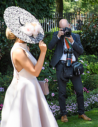 © Licensed to London News Pictures. 21/06/2018. London, UK. A photographer takes a picture of a woman posing on Ladies Day at Royal Ascot at Ascot racecourse in Berkshire, on June 21, 2018. The 5 day showcase event, which is one of the highlights of the racing calendar, has been held at the famous Berkshire course since 1711 and tradition is a hallmark of the meeting. Top hats and tails remain compulsory in parts of the course. Photo credit: Ben Cawthra/LNP
