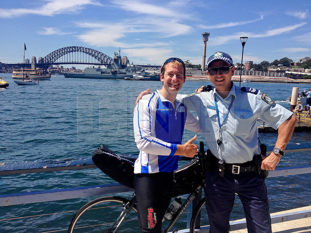 © Licensed to London News Pictures. 05/10/2013. Balmain, Sydney, New South Wales, Australia. James Ketchell world cycle/ global triathlon: posing with a friendly local police officer with the Harbour Bridge as a backdrop. The previous parts of this incredible and unique series were an Atlantic solo row in 2010 and summiting Everest in 2011.Photo credit : James Ketchell/LNP