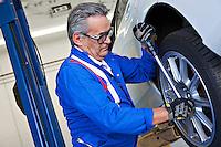 Car mechanic working on car tire