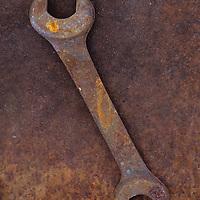 Heavy double-headed spanner lying on rusty metal sheet