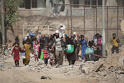 © Licensed to London News Pictures. 15/06/2017. Mosul, Iraq. Mosul residents prepare to cross the last stretch of open ground watched by Islamic State snipers to Iraqi Army positions after escaping from ISIS held territory in West Mosul today (15/06/2017).<br /> <br /> Despite heavy fighting between the Islamic State and Iraqi Security Forces many civilians have started to leave ISIS territory in West Mosul. Mosul residents, many of whom have been in hiding in their homes since the start of the West Mosul Offensive, often have to run through ISIS sniper and machine gun fire to reach the safety of Iraqi Security Forces positions. Photo credit: Matt Cetti-Roberts/LNP