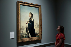 "© Licensed to London News Pictures. 05/06/2018. LONDON, UK. A staff member views ""Queen Elizabeth II"", 1955, by Pietro Annigoni at a preview of the 250th Summer Exhibition at the Royal Academy of Arts in Piccadilly, which has been co-ordinated by Grayson Perry RA this year.  Running concurrently, is The Great Spectacle, featuring highlights from the past 250 years.  Both shows run 12 June to 19 August 2018.  Photo credit: Stephen Chung/LNP"