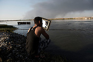 Iraq, Qayyara: On October 2016 an Iraqi army fighter shaves on the Tigris river bank. Alessio Romenzi